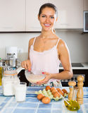 Happy girl cooking omelette with milk Royalty Free Stock Photo