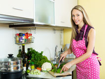 Happy girl cooking with vegetables. Cheerful young woman cooking with vegetables at  kitchen Royalty Free Stock Images