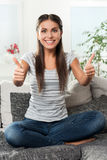 Happy girl on the couch pointing her thumbs up Royalty Free Stock Photography