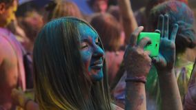 Happy girl covered in colored paint filming moments of Color fest on smartphone. Stock footage stock video footage