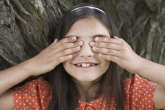 Happy Girl Covering Eyes By Tree Stock Photo
