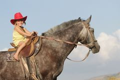 Happy girl in cowboy hat riding horse Stock Photos