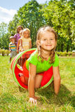 Happy girl crawl through play tube with friends Royalty Free Stock Images