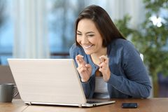 Happy girl crossing fingers checking on line content Royalty Free Stock Photo