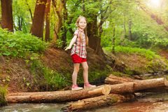Happy girl crossing a river in the forest Royalty Free Stock Image