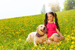 Happy girl cuddling dog sitting on the grass Stock Image