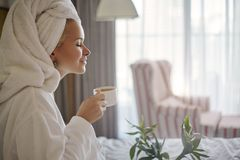 Happy Girl with a Cup of Coffee. Home Style Relaxation Woman Wearing Bathrobe and Towel after Shower. Spa Good Morning. Beautiful Luxury Life. Breakfast. Happy stock image