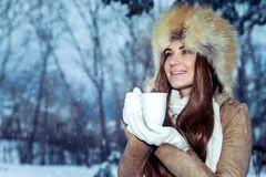 Happy girl with cup of tea in the winter park stock images