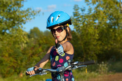 Happy girl cycling outdoors Stock Image