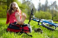 Happy girl cyclist enjoying relaxation sitting barefoot in spring park. Happy girl cyclist enjoying relaxation sitting barefoot outdoors in spring sunny park Royalty Free Stock Photography