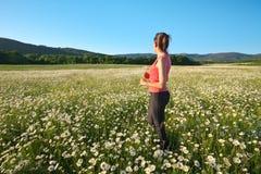 Girl in daisy wheel spring flower field stock photography
