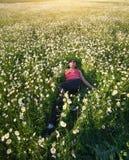 Girl in daisy wheel spring flower field stock image