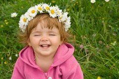 Happy girl with daisy wreath. Happy laughing girl with daisy wreath on the spring meadow stock photography
