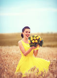Happy girl dances in summer wheat field, with bouquet of carving peaches Royalty Free Stock Images