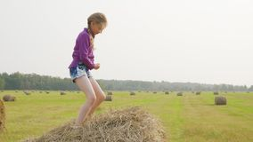 Happy girl dancing on haystack at harvesting field. Cheerfullteenager girl dancing on hay stack in countryside. Young stock video