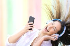 Happy girl dancing listening to music holding phone stock images