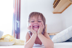 Happy girl daughter smiling and making faces looking at camera on parent`s bed at morning. Happy relaxed family life. With children at home. Bright sunny light Stock Image