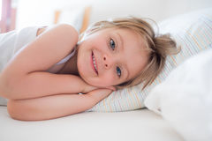 Happy girl daughter waking up smiling looking at camera on parent`s bed at morning. Happy relaxed family life with. Children at home. Bright sunny light Royalty Free Stock Image