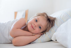 Happy girl daughter waking up smiling looking at camera on parent`s bed at morning. Happy relaxed family life with Royalty Free Stock Photo