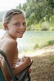 Happy Girl On Deckchair By Lake Stock Photo