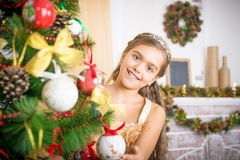 Happy girl decorates Christmas tree. Royalty Free Stock Photos
