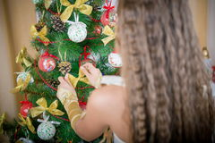 Happy girl decorates Christmas tree. Stock Photography