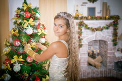 Happy girl decorates Christmas tree. Royalty Free Stock Image