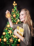 Happy girl decorating Christmas tree Royalty Free Stock Image
