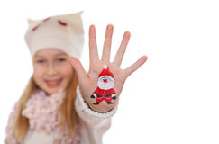 Happy girl demonstrating Christmas symbol painted on her hand. Santa Royalty Free Stock Photography