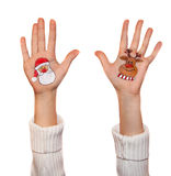 Happy girl demonstrating Christmas symbols painted on hands. Santa Claus and reindeer Royalty Free Stock Photography
