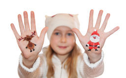 Happy girl demonstrating Christmas symbols painted on her hands Royalty Free Stock Photography