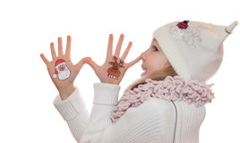 Happy girl demonstrating Christmas symbols painted on her hands. Santa Claus and reindeer Royalty Free Stock Images