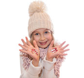 Happy girl demonstrating Christmas symbols painted on her hands. Santa Claus and reindeer Royalty Free Stock Image