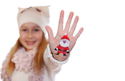 Happy girl demonstrating painted Christmas symbols on her hands. Stock Photos