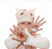 Happy girl demonstrating painted Christmas symbols on her hands. Stock Images