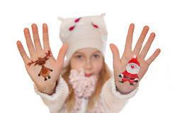 Happy girl demonstrating painted Christmas symbols on her hands. Royalty Free Stock Images