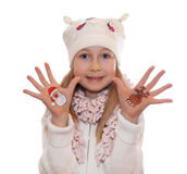 Happy girl demonstrating painted Christmas symbols on her hands. Stock Photo