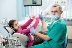 Happy girl in dentist chair educating proper tooth-brushing, using dental jaw model and toothbrush in dental office. Pediatric dentist showing thumbs up stock photography