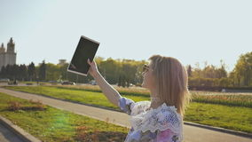 A happy girl does selfie with a tablet on a warm evening at sunset. stock video footage