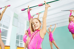 Happy girl doing gymnastic exercises with clubs. Close-up portrait of happy 11 years old girl wearing pink leotard, doing gymnastic exercises with clubs in Stock Photos