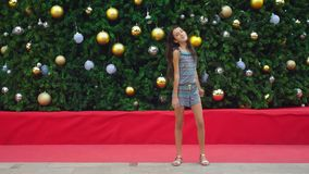 Happy girl doing gymnastic somersault on the background of the Christmas tree and palm trees in a tropical city. The royalty free stock photo