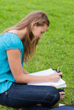 Happy girl doing her homework while sitting down Stock Image