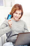 Happy girl doing on line shopping with credit card. From home Royalty Free Stock Photos