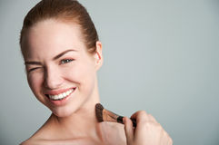Happy girl doing makeup on gray Stock Photo