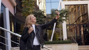 Happy girl doing selfie photo on the smartphone device camera and posing near modern building background. Outdoors. Urban street, lifestyle, 4k stock footage