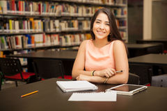 Happy girl doing some homework. Cute young Hispanic woman doing some homework at the school library and smiling stock photo