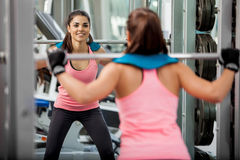 Happy girl doing some squats. Beautiful young woman doing some squats with a barbell and smiling at the gym Royalty Free Stock Photos