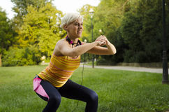 Happy girl doing squats in park, closeup royalty free stock photo
