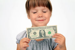 The happy girl with dollar in hands. Has closed eyes from pleasure on a white background Royalty Free Stock Image