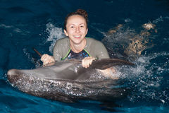 Happy girl and dolphin. Photo happy girl and dolphin in blue water royalty free stock images